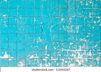 Grunge texture of blue broken tiles on old wall