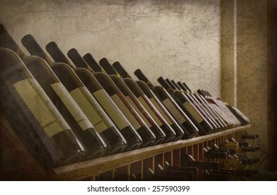 A grunge textured photo of several bottles of wine on a wine rack. Perfect display of different varieties.