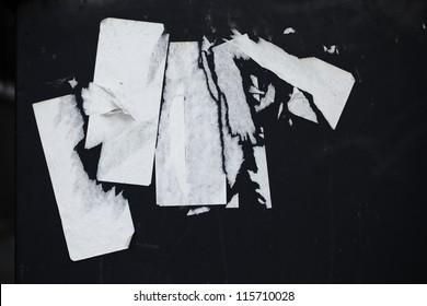 Grunge white paper stickers torn off black background