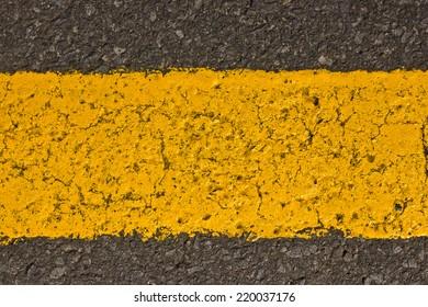 Grunge yellow paint line on asphalt.