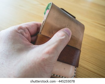 Grunged and dirty leather wallet on wooden table. Hand grab leather wallet.