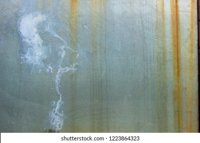 Grungey blue-grey metal sheet with stained rusting orange lines running down from the top and white paint splash