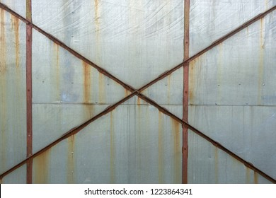 Grungey gray metal sheet with rusted metal cross braces and stained rusting orange lines running down