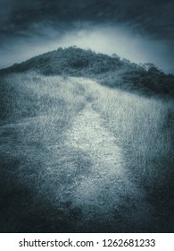 grungy abstract image of monochrome mountain view with grass field and pathway in lonely sad feel bitter cold and dark sky