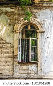 Grungy arched casement window in wall with plaster peeling off exposing bricks underneath - striped curtains and plants in open window - untidy electric lines