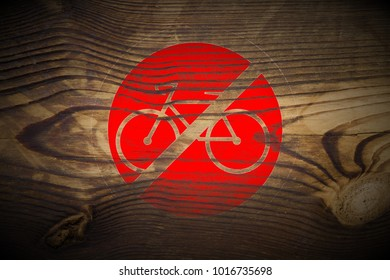 grungy bicycle ride forbidden sign painted on dark brown wood texture background