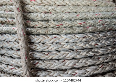 Grungy and coarse nautical thick rope rolled-up in a coil