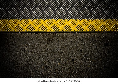 grungy, dirty view of asphalt with distinct yellow stripe on metal surface