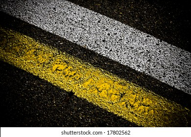 grungy, dirty view of asphalt with distinct yellow and white stripes