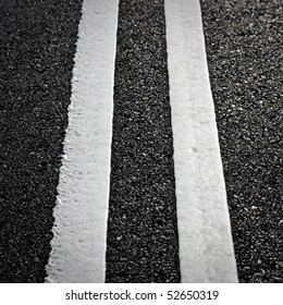 grungy, dirty view of asphalt with distinct white stripes