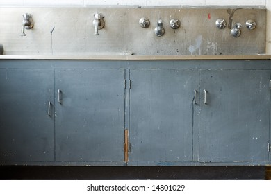 A grungy, dirty wash basin, actually shot in a class room but could be anywhere. Broken cupboard doors and loose handles