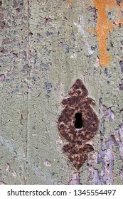 Grungy door with cracked paint and rusty keyhole.