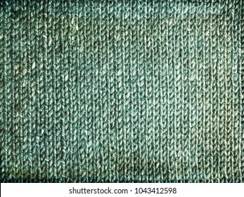 Grungy faded green knitted background. Handcrafted rustic canvas.