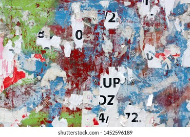 Grungy flat wall surface covered with pealed paper and red, green and blue spray paint