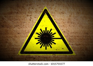 grungy laser beam warning sign painted on scratched wooden board texture background