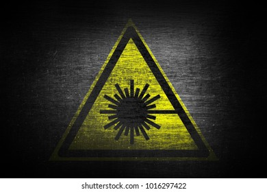 grungy laser beam warning sign painted on scratched metal surface texture background