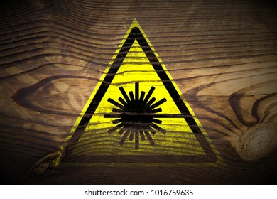 grungy laser beam warning sign painted on dark brown wood texture background