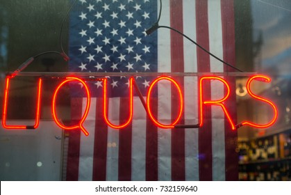 grungy Liquors neon sign in the window of a Liquor store with unites states flag background