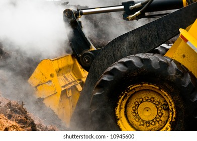 grungy loader scoops up steaming mulch