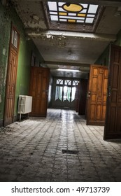 A grungy looking hallway, with open wooden doors. Shot taken at an old abandoned building, build in the beginning of 1900.