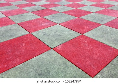 A grungy maroon checker matrix synthetic rubberized flooring.