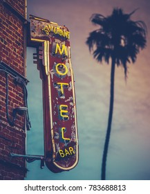 Grungy Motel Restaurant Bar Neon Sign Against A Palm Tree At Sunset