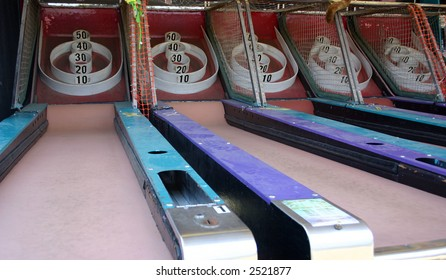 Grungy old carnival games; roll the ball into the holes to get points