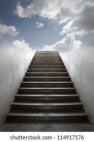 A grungy old concrete staircase going up into a blue cloudy sky.