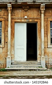 Grungy old door of an old stone house with columns