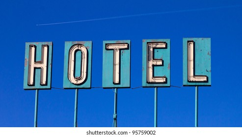 Grungy old hotel sign isolated on a blue sky background with an airplane flying in the distance