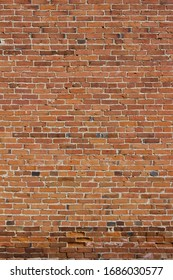 Grungy old red brick wall texture background with deterioration from age