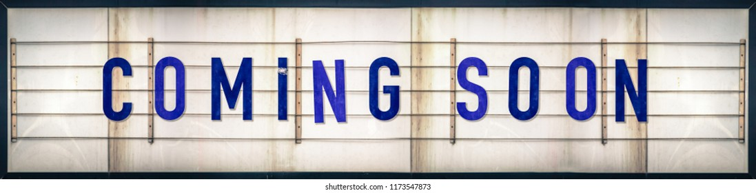A Grungy Old Weathered Coming Soon Marquee Sign With Blue Letters