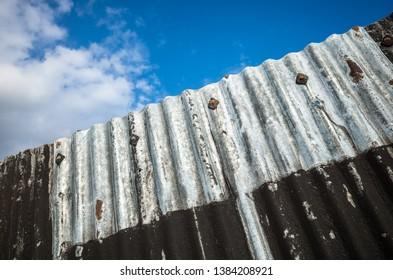 Grungy,  old weathered corrugated iron fence.