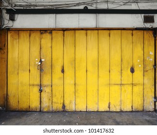 A grungy old yellow color metal folding door on the shopfront of an old workshop.