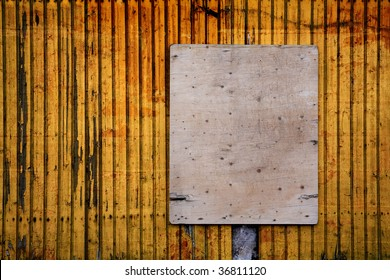 Grungy plate on yellow, wooden wall, free copy / ad space