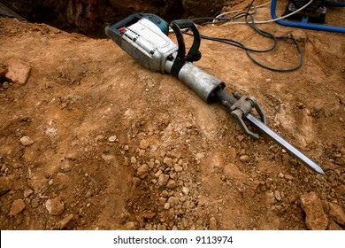 Grungy pneumatic hammer lying on the ground