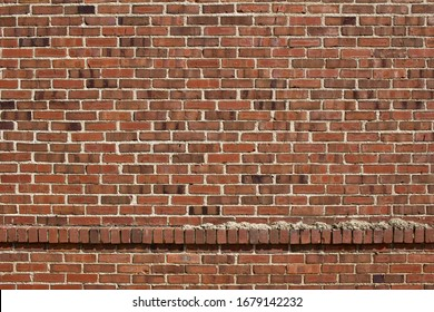 Grungy red and brown brick wall background with shabby chic texture, showing an accent row of protruding bricks
