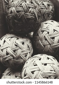 grungy style black and white of close up basketry rattan balls stack, high contrast image  and contain film grain