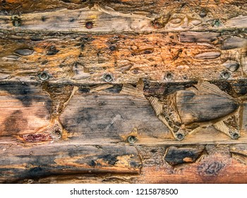 grungy texture of brown planks of wood wit nails covered with peeling varnish and burn stains
