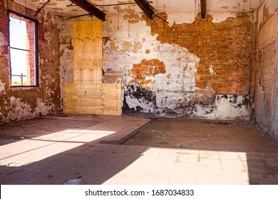 Grungy textured interior of an abandoned and derelict building with flaking walls and exposed  brick and timber beams