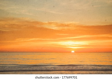 Grungy and vintage filtered colorful sunset on the ocean.