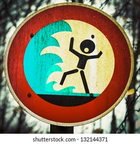 Grungy warning sign for flash flood  flooding  big tidal waves or tsunami with a pictorial signboard showing a person shouting out in panic about to be engulfed by high water