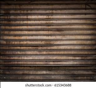 Grungy weathered metallic roll up door. Rusty iron gate.