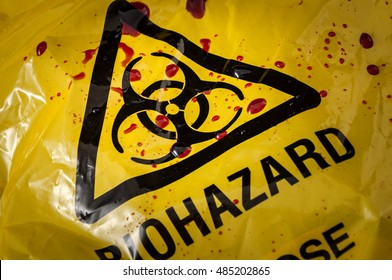 Grungy worn and beat up yellow biohazard bag and spilled blood and biological waste