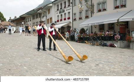 Gruyere, Switzerland - July 19, 2014. Swiss musicians play the folk national musical instrument alphorn in the Gruyere village.