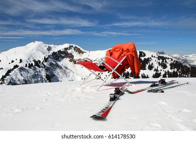 GRYON, SWITZERLAND - 19 MARCH 2017: Skis lie next to a reclining chair at a ski resort in the Swiss Alps. Around 120 million tourists visit the 4,200 km2 of ski runs in the Alps every year. Editorial.