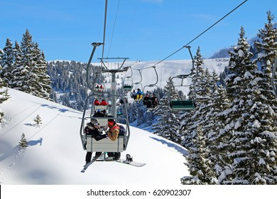 GRYON, SWITZERLAND - 9 MARCH 2016: A skier & a snowboarder on a chair lift at an alpine ski resort. Around 120 million tourists visit the 4,200 km2 of ski runs in the Alps every year. Editorial.