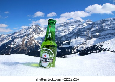 GRYON, SWITZERLAND - 9 MARCH 2016: A bottle of Heineken in the snow in an alpine setting. Heineken is the world's 9th biggest beer brand, grossing over ?€10 billion in revenue annually. Editorial.