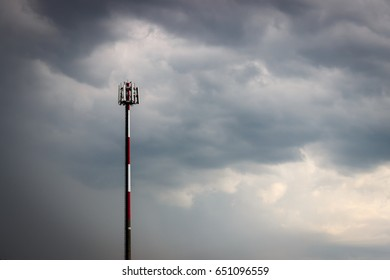 GSM antenna tower (transmitter, transceiver), red and white striped pole, stormy cloudy sky.