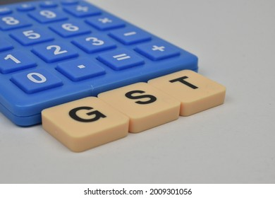 GST alphabet and blue calculator with white background. GST stands for Goods and Services Tax